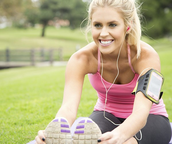 young woman stretching outdoors listening to music through earphones