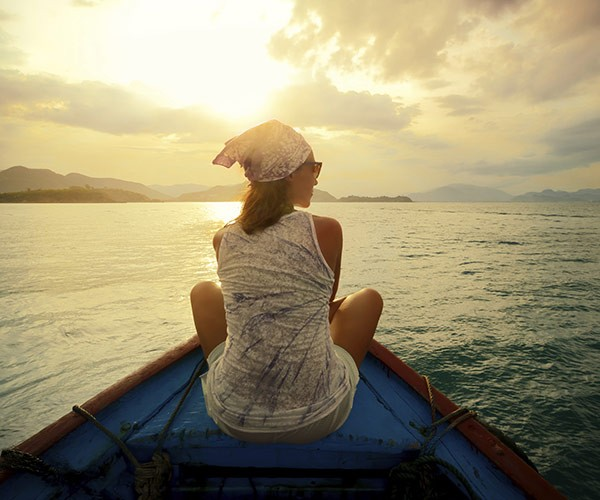 Back of woman riding canoe during sunset
