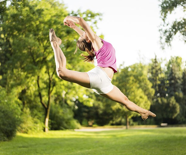 Woman in ballet pose mid air outdoors