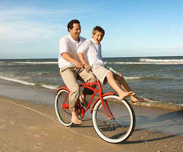 Father with son on handlebars riding bike along beach shoreline