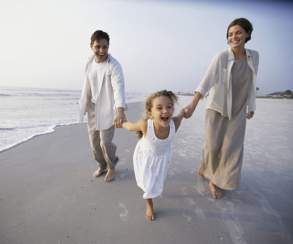Young couple holding hands with toddler along beach shoreline
