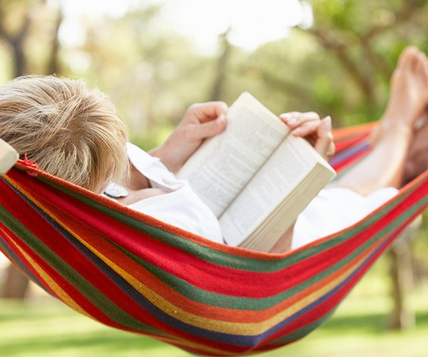 close up of middle aged woman lying on hammock reading book