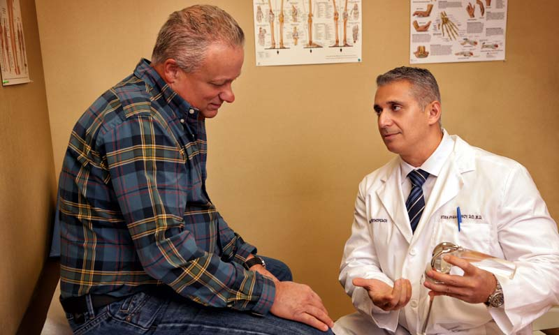 Doctor consulting patient's knee injury
