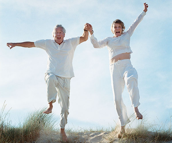 Middle aged couple jumping and smiling at beach