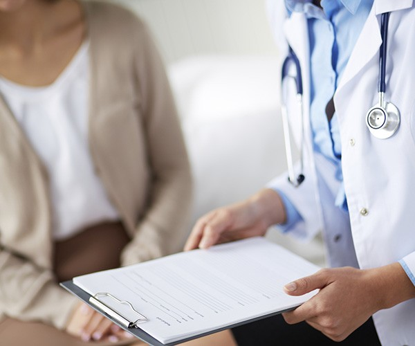 close up of doctor consulting patient chart