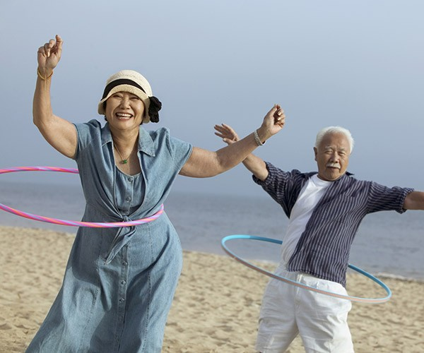 Asian middle aged couple with hoola hoops at beach