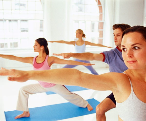 Women doing indoor pilates, arms outstretched